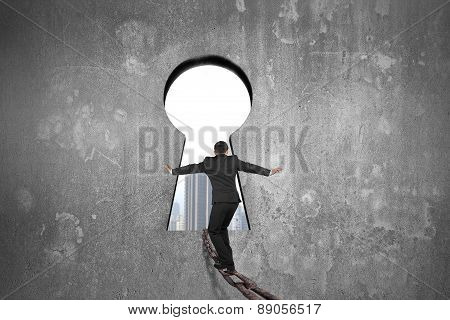 Businessman Balancing On Iron Chain Toward Keyhole With Urban Scene