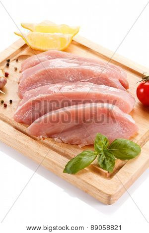 Raw chicken fillets on cutting board on white background