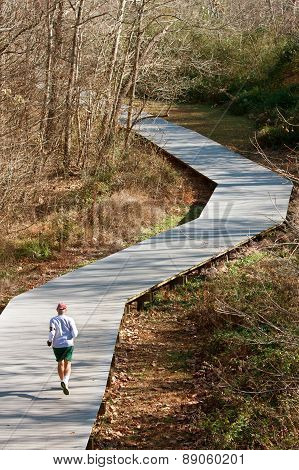 Senior Man Runs On Jogging Trail Made Of Wood Decking