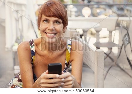 Happy adult woman sending text message
