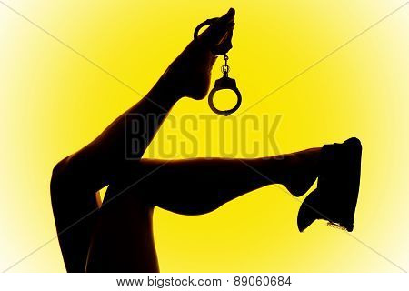 Silhouette Of Woman Legs Handcuffs And Hat Yellow