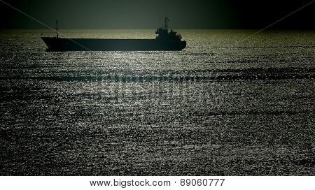 Silhouette Of A Merchant Ship In A Twilight Sea