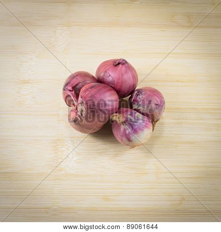 Shallots (red Onion) Set Up On Wood Table