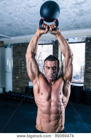 Bodybuilder man workout with kettle ball in gym