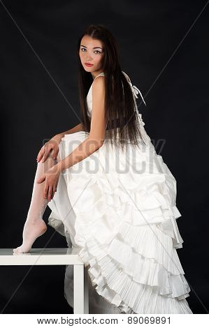bride in a wedding dress straightens stockings