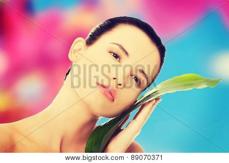 Beautiful woman with artistic make up and bamboo leaves