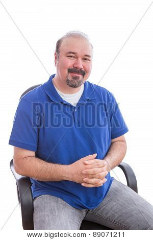 Admiring Bearded Man On A Chair Looking At Camera
