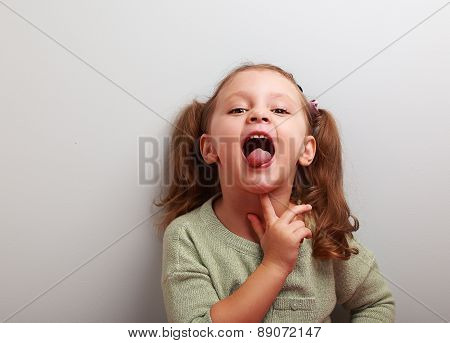 Thinking Playful Kid Girl Showing Tongue. Closeup Portrait With Copy Space