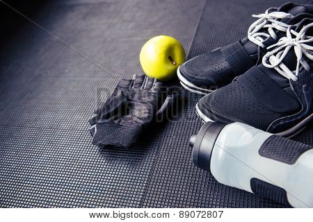 Closeup image of a sports gloves, sneakers, bottle with water and green apple on rubber floor