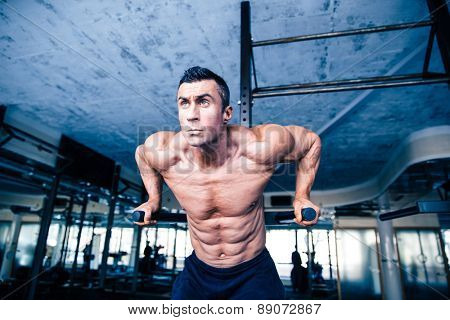 Young muscular man workout on bars at gym