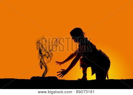 Silhouette Of A Cave Woman Kneel By Fire