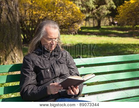 Haired Elderly Man Reading A Book Sitting On A Bench In City Park