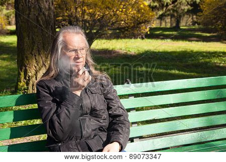Elderly Gray-haired Man In Glasses Smoking A Cigarette In City Park