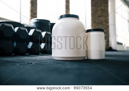 Closeup image of a plastic containers with sports nutrition in gym