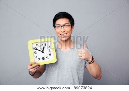 Happy asian man holding big clock and showing thumb up over gray background and looking at camera