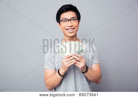 Cheerful man in glasses holding bills of US dollars over gray background and looking at camera