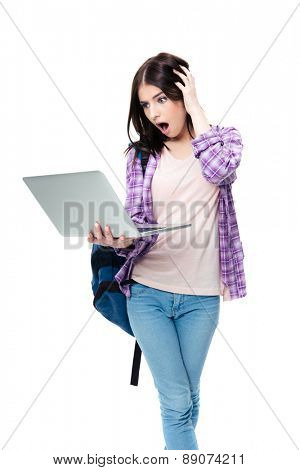 Surprised woman standing and looking on laptop screen over white background