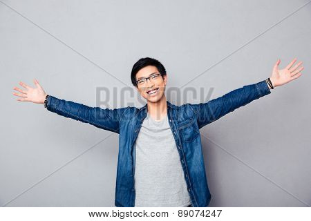 Happy asian man greeting somebody over gray background. Looking at camera