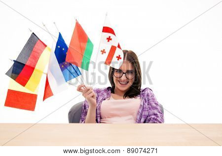 Happy young woman sitting at the table with international flags over white background and looking at camera