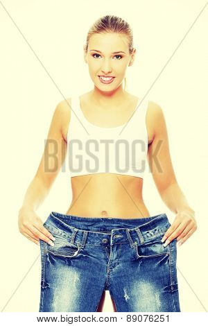 Slim woman with too large jeans