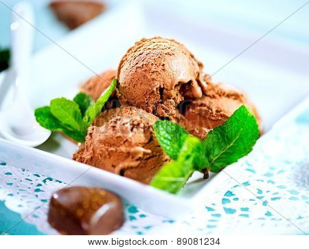 Ice cream scoops with chocolate topping. Brown chocolate icecream served with dark chocolate topping and mint