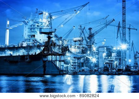 Shipyard at work, ship repair. Industrial machinery, cranes. Transport, freight concept
