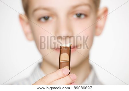 Portrait of a boy holding milk chocolate bar