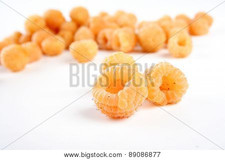 Close-up of yellow raspberries on white background