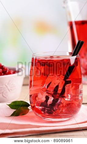 Compote with red currant in glassware on wooden table on light blurred background