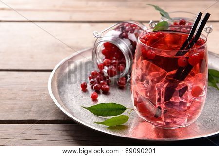 Compote with red currant in glassware on metal tray on wooden table, closeup