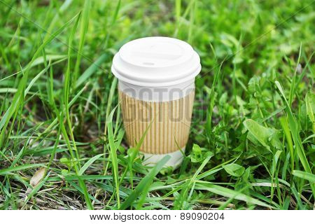 Paper cup on green grass background