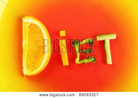 Word DIET made of sliced vegetables on color plate background