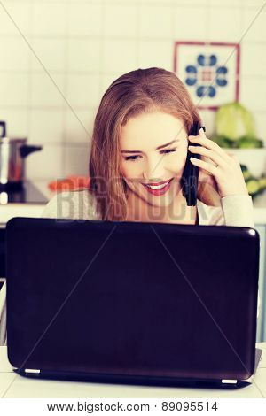 Portrait of happy blond woman using laptop