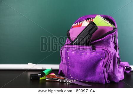 Gun in school backpack on wooden desk, on blackboard background