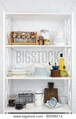 Kitchen shelving with dishes on white brick wall background