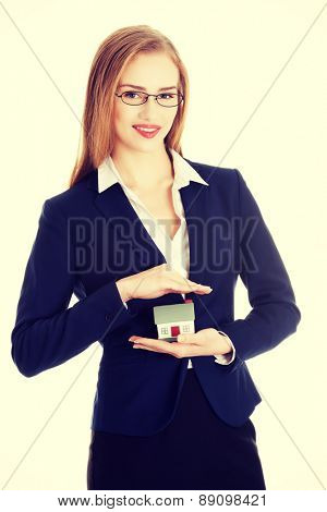 Beautiful businesswoman holding a model of house