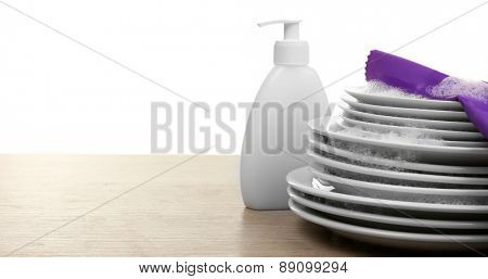 Plates in foam with gloves and cleanser on table isolated on white