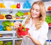 stock photo of strawberry blonde  - Portrait of a beautiful female standing near open fridge full of fruits and vegetables - JPG