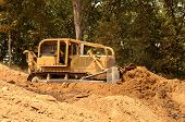 picture of bulldozer  - Exchavator bulldozer pushes top soil and loose dirt down a hill at a new commercial construction development project - JPG
