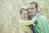 pic of bonding  - Caucasian mother and daughter hugging smiling and sharing a tender bonding moment amongst meadow grass - JPG
