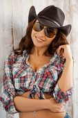 image of cowgirls  - Beautiful young cowgirl posing while standing against thewooden background - JPG