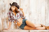 pic of cowgirls  - Beautiful young cowgirl adjusting her hat and looking at camera while sitting against thewooden background - JPG