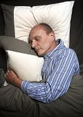 stock photo of pajamas  - Man in pajamas or jammies sleeping in bed - JPG