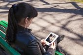 stock photo of black pants  - young beautiful woman in a black leather jacket and black pants sitting on a park bench looking at a photo on the tablet - JPG
