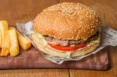 image of beef-burger  - Delicious burger with beef tomato cheese and lettuce on paper and fries on wooden table - JPG