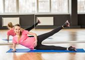 foto of pregnancy exercises  - Smiling pregnant woman at gym fitness exercise practicing aerobics on mat - JPG
