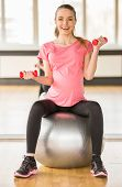 stock photo of pregnancy exercises  - Young pregnant woman doing exercise using a fitness ball and dumbbells - JPG