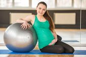 image of pregnancy exercises  - Young pregnant woman doing exercise using a fitness ball - JPG