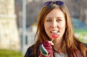 picture of love bite  - Girl biting heart shape candy on a sunny day outdoors - JPG