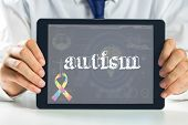 picture of autism  - The word autism and autism awareness ribbon against medical biology interface in blue - JPG